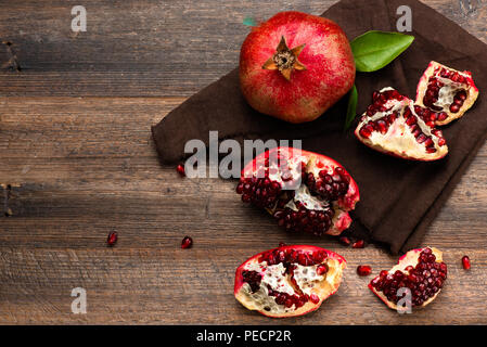 Pomegranate fruits with grains on wooden table. Top view. - Stock Photo
