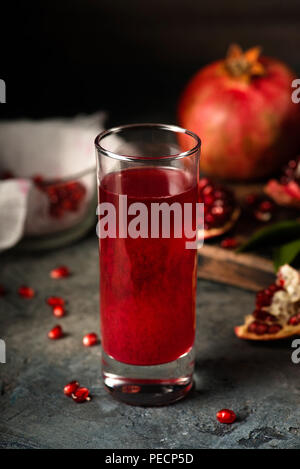 Glass of pomegranate juice. fruits with grains and leaves on the table. Make . Dark moody. - Stock Photo