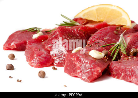 Pieces of meat with garlic, lemon and rosemary on wooden board isolated. Raw beef. - Stock Photo