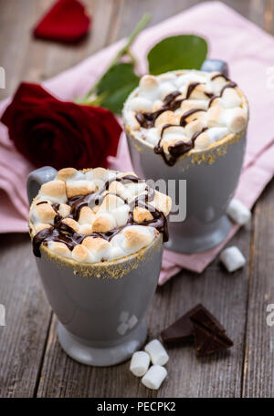 S'mores drink. Two mugs of hot chocolate with marshmallows on a wooden table. Cocoa. Rose petals. Valentine. - Stock Photo