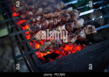 Shashlik preparing on a barbecue grill over charcoal. Pieces of meat on skewers. Shish kebab prepare on fire. - Stock Photo