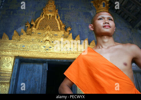Stunning portrait of Buddhist novice young monk in Wat Xieng Thong monastery in Luang Prabang, Laos - Stock Photo