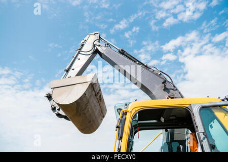 Bucket of yellow excavator loader standing against sunny cloudy sky during road construction and repairing asphalt pavement works - Stock Photo