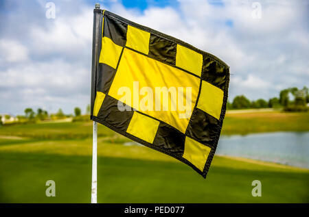 Yellow flag on golf course green with water hazard in the background. - Stock Photo
