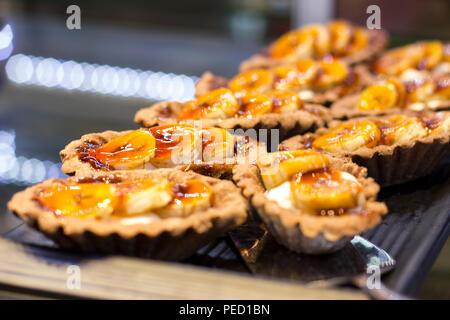 Tartlets with fresh bananas on black tray - Stock Photo