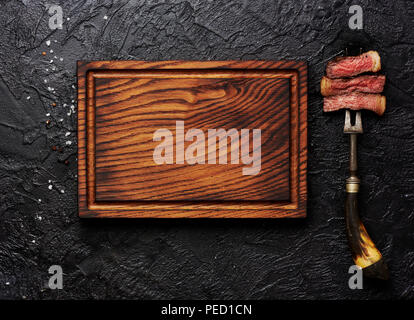 Slices of medium rare grilled Steak on meat fork on black concrete background. Copy space. Wooden meat cutting board. Top view. - Stock Photo