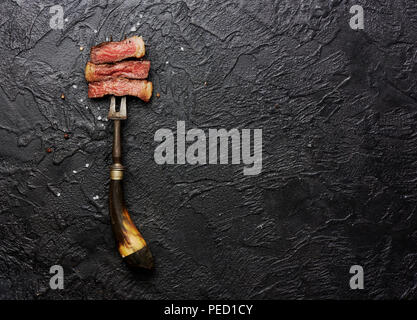Slices of medium rare grilled Steak on meat fork with salt and pepper on black concrete background. Copy space. Top view. - Stock Photo