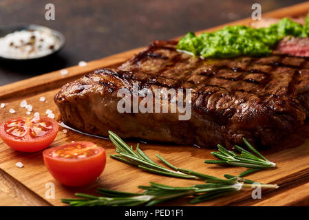 Grilled Black Angus Steak with tomatoes, garlic with chimichurri sauce on meat cutting board. - Stock Photo