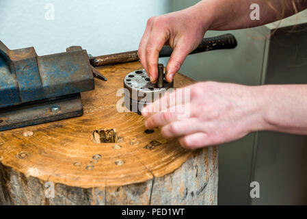 Compactor and other working equipment of a goldsmith with both hands manufacturing jewelry out of raw metal - Stock Photo