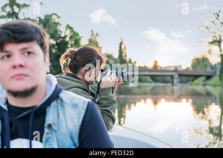 Woman with a camera takes pictures of the nature from the boat, sailing along the river - Stock Photo