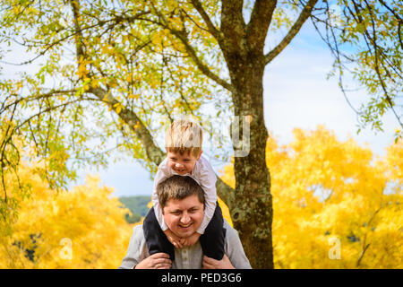Father giving his son piggyback ride in autumn park, Adelaide Hills, South Australia - Stock Photo