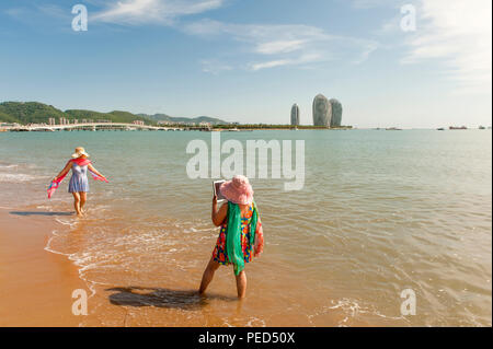Two Chinese ladies taking pictures of each other at the public beach of Sanya, with Phoenix Island in the distance - Stock Photo