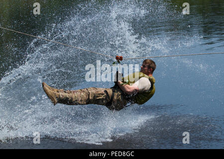 U.S. Army Sgt. Andrew Boulanger, a Soldier with P Troop, 4th Squadron, 2nd Cavalry Regiment, competes in water obstacle course Aug. 5, 2015, at the Nowa Deba Training Area in Poland. The obstacle course was put together by Polish soldiers from the 6th Airborne Brigade. The training is part of Operation Atlantic Resolve, an ongoing multinational partnership focused on joint training and security cooperation between NATO allies. Led by the mission command element of the 4th Infantry Division and in conjunction with European partner nations, Atlantic Resolve is intended to improve joint operation - Stock Photo