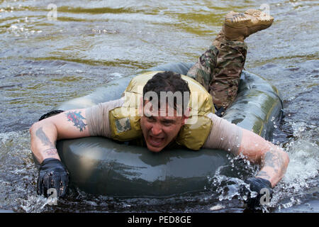 U.S. Army 1st Sgt. Jefferey Crossman, a Soldier with P Troop, 4th Squadron, 2nd Cavalry Regiment, crosses a lake Aug. 5, 2015, at the Nowa Deba Training Area in Poland. Crossman is participating in an obstacle course created by Polish soldiers from the 6th Airborne Brigade. The training is part of Operation Atlantic Resolve, an ongoing multinational partnership focused on joint training and security cooperation between NATO allies. Led by the mission command element of the 4th Infantry Division and in conjunction with European partner nations, Atlantic Resolve is intended to improve joint oper - Stock Photo