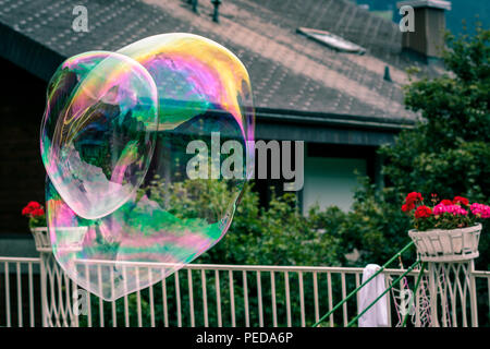 2 big rainbow soap bubbles flyining in the air on a garden background - Stock Photo