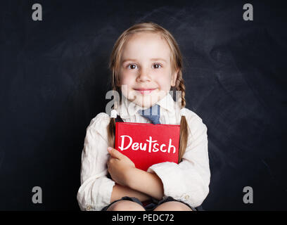 Speak german and learn language concept. Child schoolgirl holding red book on chalkboard background. - Stock Photo