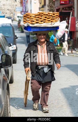 Typical Simitci Turkish man selling simit - turkish sesame bread rings in streets of Istanbul, Republic of Turkey - Stock Photo