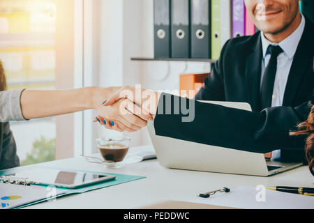 Close up Business women shaking hands during a meeting in the office with blurred business happiness people :business team partnership concept - Stock Photo