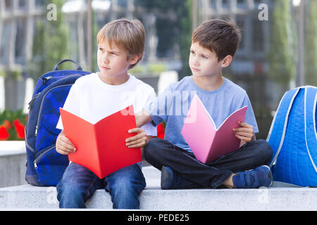Schoolboys learning reading, doing homework after school outdoors - Stock Photo