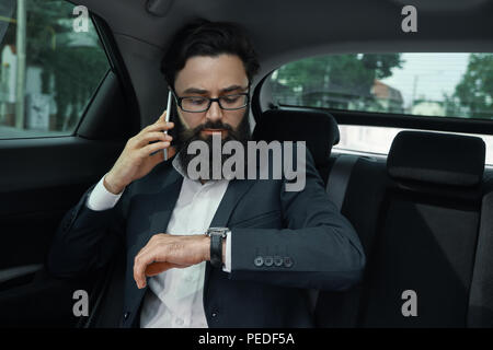 A businessman while traveling by car in the back seat using a sm - Stock Photo