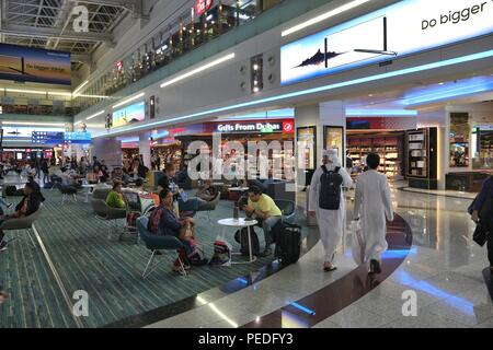 DUBAI, UAE - NOVEMBER 23, 2017: Passengers wait at Dubai International Airport, United Arab Emirates. It is the 3rd busiest airport in the world with  - Stock Photo
