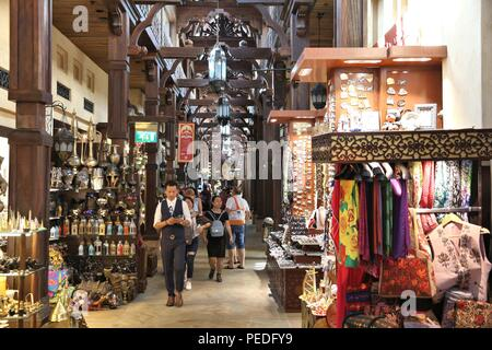 DUBAI, UAE - NOVEMBER 23, 2017: People shop at Souk Madinat Jumeirah in Dubai. The traditional Arab style bazaar is part of Madinat Jumeirah resort. - Stock Photo