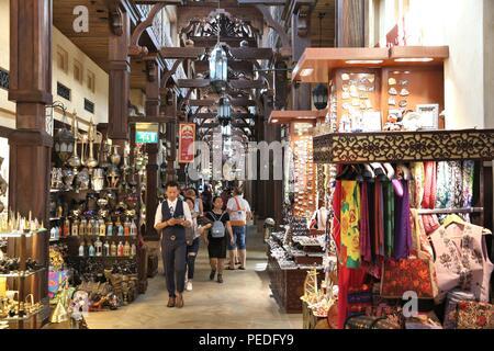 DUBAI, UAE - NOVEMBER 23, 2017: People shop at Souk Madinat Jumeirah in Dubai. The traditional Arab style bazaar is part of Madinat Jumeirah resort. - Stock Photo