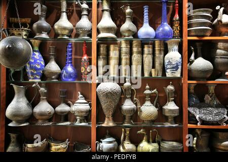 DUBAI, UAE - NOVEMBER 23, 2017: Antique brass jugs and glass vases at Souk Madinat Jumeirah in Dubai. The traditional Arab style bazaar is part of Mad - Stock Photo