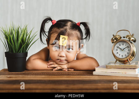 cute and confused lookian asian toddler with question mark on her forehead. concept of child learning education, growth and development. - Stock Photo