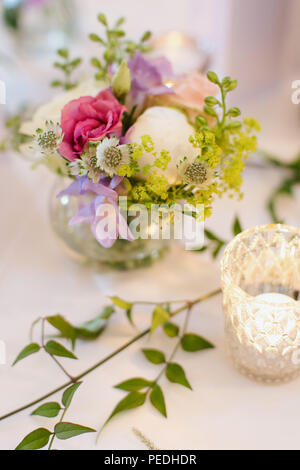 Pretty posies of English country garden flowers in vases. Table decor, decoration, party ideas - Stock Photo