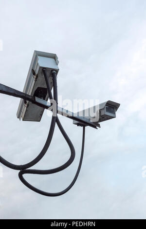 Two security cameras facing in different directions on a metal arm - Stock Photo