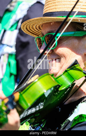 Traditional English folk dancer musician, senior woman playing a green fiddle with the Offcumduns Northwest Clog dance side. Close up of violinist. - Stock Photo