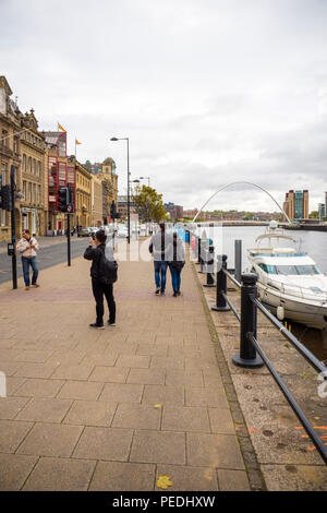 Tourists taking pictures of each other on the Newcastle Quayside, with the Millennium Bridge and Baltic Centre For Contemporary Arts in the background - Stock Photo