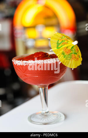 Red frozen drink with cocktail umbrella in front of a jukebox - Stock Photo