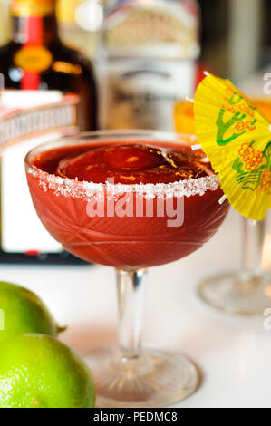 Strawberry frozen Martini / Daiquiri in front of blurred alcoholic bottles - Stock Photo