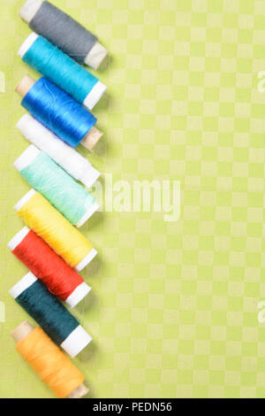 Colorful thread in spools on green background 2018 - Stock Photo