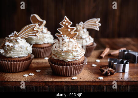 Homemade gingerbread cupcakes decorated with cinnamon and Christmas cookies and snowflake sprinkles - Stock Photo