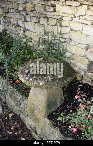 Staddle stone in a garden border retaining wall, a stone wall behind in the Cotswold England. The Mushroom shaped stones used for building support. - Stock Photo