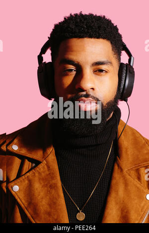Portrait of a cool man with beard and headphones isolated on pink studio background - Stock Photo