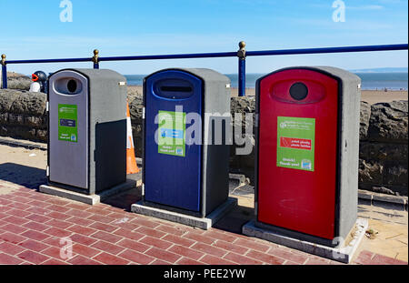 Colour coded litter bins with dual-language posters on the promenade at Barry Island, Wales - Stock Photo