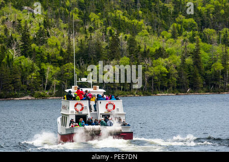 Tourists aboard the West Brook II for a waterfall & wildlife watching trip on Western Brook Pond in Gros Morne National Park, Newfoundland. - Stock Photo