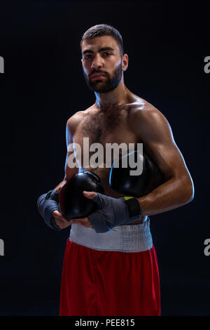 Handsome athletic guy in a red shorts on a black background. The boxer is fetching his breath after practicing hooks and blows. - Stock Photo