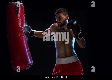 Bearded male boxer training with punching bag on black background. Male boxer as exercise for the big fight. - Stock Photo