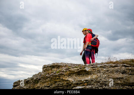 Photo from back of hugging man and woman tourist on mountain - Stock Photo