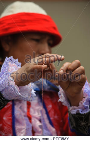 A Quechua woman in traditional dress, which indicates which village she is from, spins wool during a weaving workshop. - Stock Photo