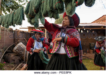 Quechua women in traditional Chinchero dress wring out freshly dyed wool and hang it to dry, during a weaving workshop at the Center for Traditional Textiles. - Stock Photo