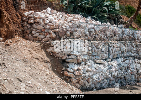 Gabion wire mesh baskets filled with stone for slope stabilization - Stock Photo