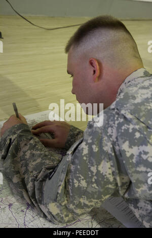 U.S. Army Staff Sgt. Charles Averitt, from 30th Armored Brigade Combat Team headquarters and assigned to Multinational Battle Group-East, plots the grid coordinates on the map during the land navigation portion of the MNBG-E Soldier of the Month competition, Aug. 1, 2015, at Camp Bondsteel, Kosovo. The competition, held by Command Sgt. Maj. Ralph Johnson, the senior noncommissioned officer for the North Carolina National Guard's 30th ABCT as well as MNBG-E, was broken into two categories, one for junior enlisted Soldiers, and another for sergeants and staff sergeants. The day led off early tha - Stock Photo