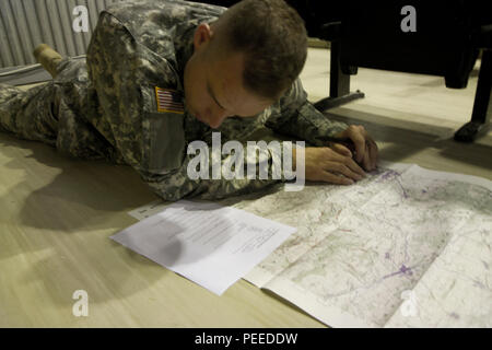U.S. Army Sgt. Sterling Quimby, from 1st Battalion, 169th Aviation Regiment and assigned to Multinational Battle Group-East, plots the grid coordinates on the map during the land navigation portion of the MNBG-E Soldier of the Month competition, August 1, 2015, at Camp Bondsteel, Kosovo. The competition, held by Command Sgt. Maj. Ralph Johnson, the senior noncommissioned officer for the North Carolina National Guard's 30th Armored Brigade Combat Team as well as MNBG-E, was broken into two categories, one for junior enlisted Soldiers and another for sergeants and staff sergeants. The day led of - Stock Photo