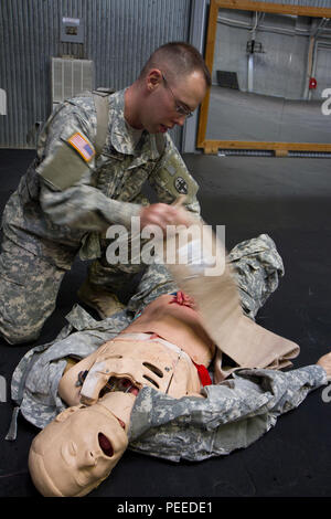 U.S. Army Spc. Robert McDonald, from the 345th Combat Support Hospital and assigned to Multinational Battle Group-East, prepares an injured soldier for medevac during the first aid portion of the MNBG-E Soldier of the Month competition, Aug. 1, 2015, at Camp Bondsteel, Kosovo. The competition, held by Command Sgt. Maj. Ralph Johnson, the senior noncommissioned officer for the North Carolina National Guard's 30th Armored Brigade Combat Team as well as MNBG-E, was broken into two categories, one for junior enlisted Soldiers and another for sergeants and staff sergeants. The day led off early tha - Stock Photo
